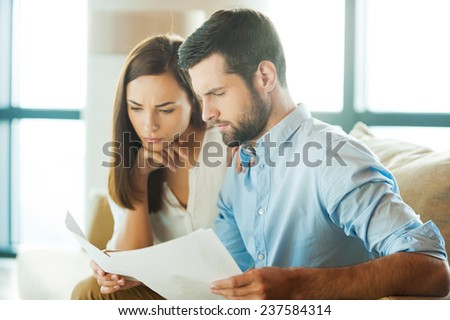Examining documents together. Concentrated young man holding documents and looking at them while woman sitting close to him and holding hand on chin  - stock photo