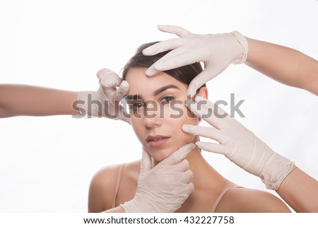 Examining face concept. Portrait of surgery examination before injection. Beautiful lady having examination of her face by cosmetologists over white background.