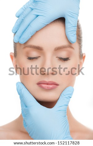 Examining face. Portrait of beautiful young woman with closed eyes and hands in gloves examining her face - stock photo