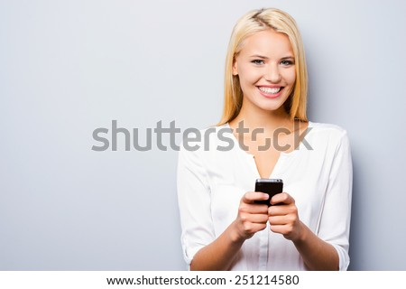 Examining her brand new smart phone. Beautiful young blond hair women holding smart phone and smiling while standing against grey background - stock photo