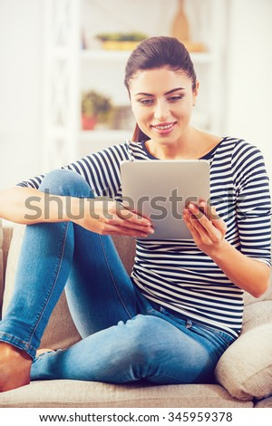 Examining her brand new tablet. Beautiful young woman holding digital tablet and looking at it with smile while sitting on the couch at home  - stock photo