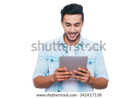 Examining his brand new gadget. Handsome young Indian man holding digital tablet and looking at it with smile while standing against white background - stock photo