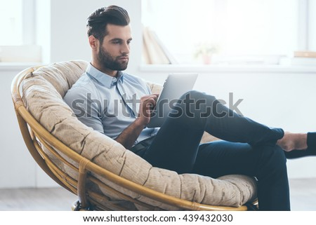 Examining his new tablet. Confident young handsome man working on digital tablet while sitting in big comfortable chair at home   - stock photo
