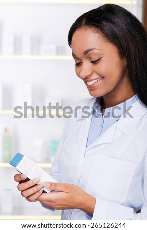 Examining new medicine. Beautiful young African woman in lab coat holding container with some medicine and looking at it with smile while standing in drugstore  - stock photo