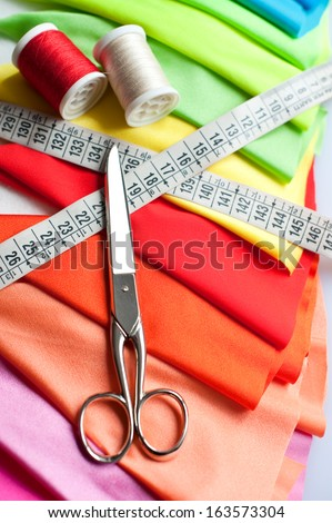 Example of Colorful fabric, scissors, meter and threads - stock photo