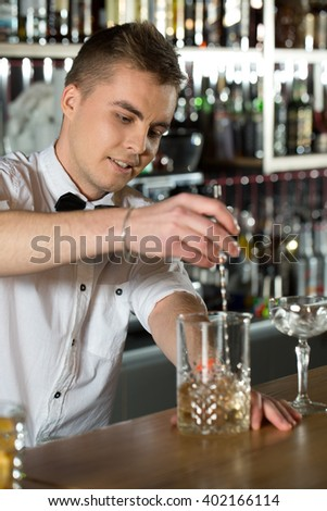 Example of hospitality. Attractive young bartender making a drink smiling.