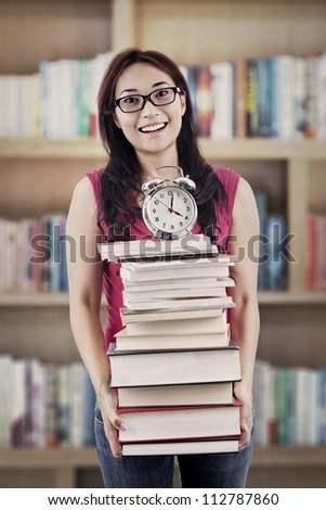 Exams time concept: college student prepares a pile of textbooks and alarm clock for preparing exams - stock photo