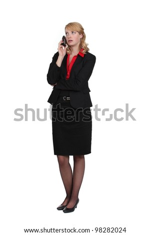 Exasperated woman talking on her mobile phone - stock photo