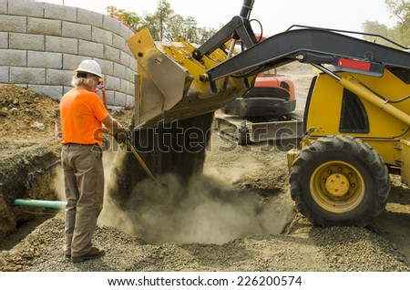 Excavation construction contractor installing a domestic black plastic sewer drain on a new commercial street filling utilities ditch with gravel - stock photo