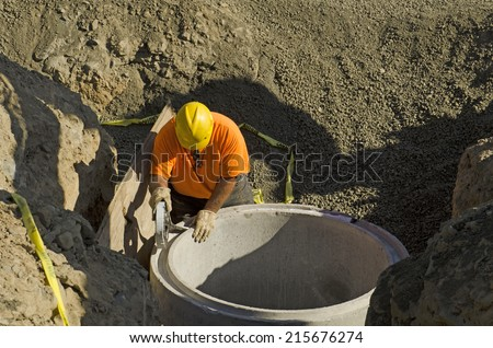 Excavation contractor installing a riser on a manhole vault on a sanitary sewer system on a new commercial development - stock photo