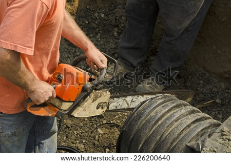 Excavation contractor uses a chain saw to cut plastic drain pipe for a new commercial street storm drain sewer - stock photo