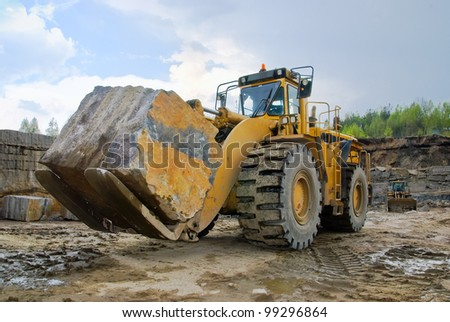 Excavation with a big stone  in a granite quarry - stock photo