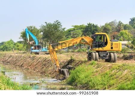 excavator along river - stock photo