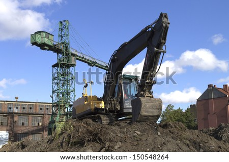 Excavator and crane at the shipyard in Gdansk - stock photo