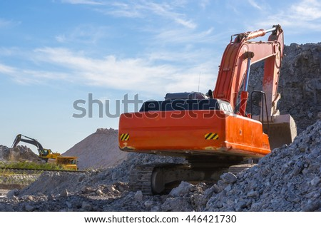 excavator and dumper - warehouse production in quarry blue clay on sky background