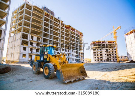 Excavator and the building under construction against the blue sky