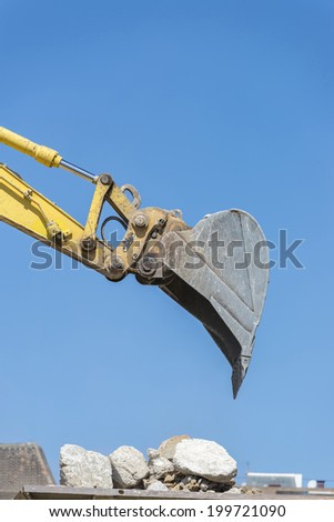 excavator arm placing sand or debris on a truck - stock photo