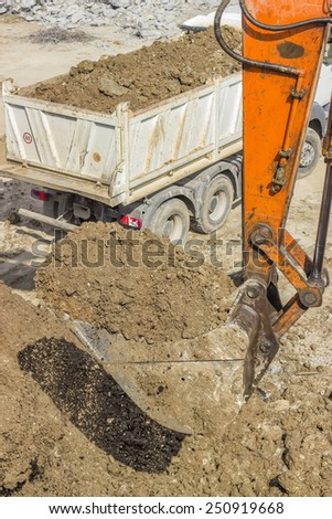 excavator arm with bucket full of dirt at construction site - stock photo