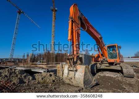 Excavator at the construction site of an apartment building - stock photo