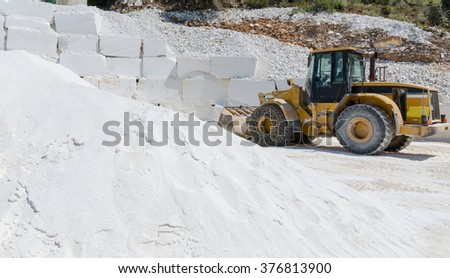 Excavator at work in a marble pit - stock photo