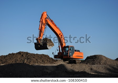 Excavator at work - Orange excavator at work in open sand mine and a blue sky - stock photo