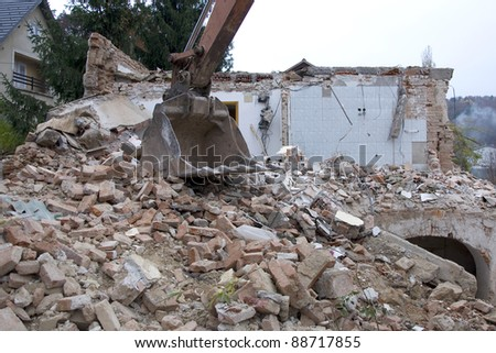 Excavator bucket, old house demolition - stock photo