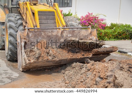 Excavator, bulldozer work a dig hole the repair of pipe water and sewerage on road - stock photo
