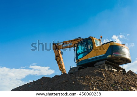 Excavator bulldozer working on a construction site with a blue sky background. - stock photo