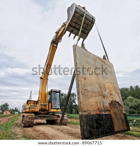 Excavator carries a large metal table - stock photo