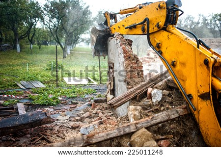 Excavator demolishing a concrete wall.bulldozer loading demolition debris and concrete waste for recycling at construction site. - stock photo