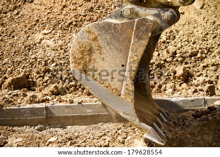 Excavator digging a deep trench, working - stock photo