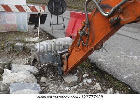 excavator digging a paved road