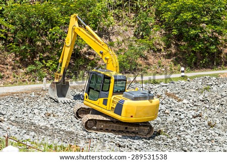 excavator digging rock on constriction site - stock photo