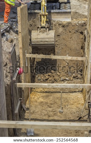 excavator digging trench for the ground piping at construction site - stock photo