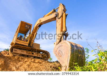 excavator in construction site against blue sky - stock photo