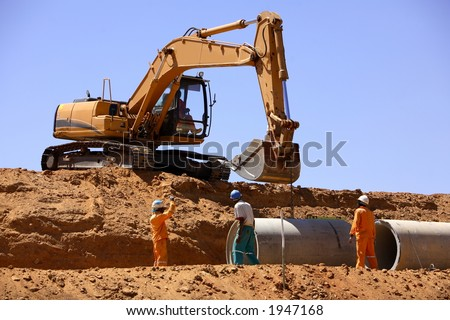 Excavator laying pipes