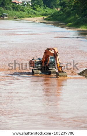 Excavator loader at river with raised bucket over blue sky - stock photo