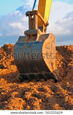 Excavator loader bucket on blue sky background.  - stock photo