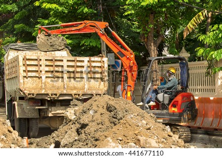 Excavator loader driver working in construction area. - stock photo