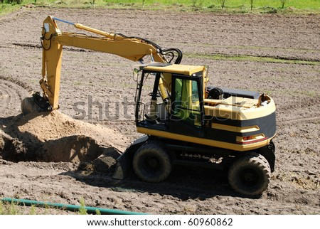 Excavator Loader standing in sandpit with pulled down bucket