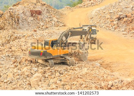 excavator loading cracked rock on dumper truck with crushed rock at dolomite mines site