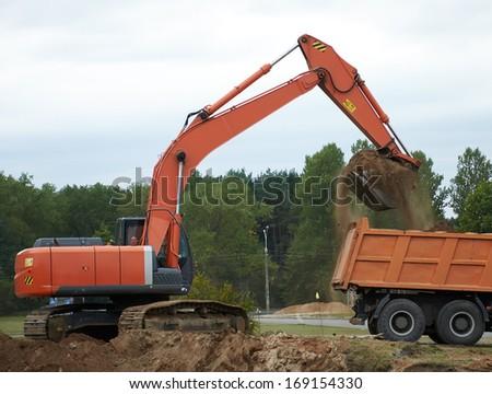 Excavator Loading Dumper Truck - stock photo