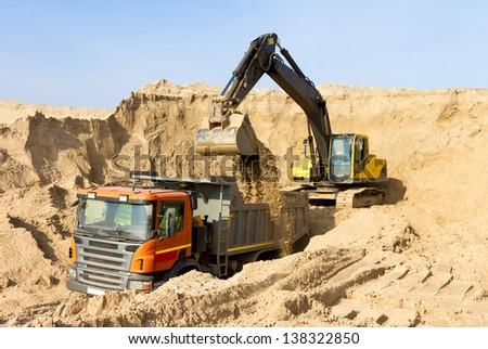 Excavator Loading Dumper Truck Construction Site - stock photo