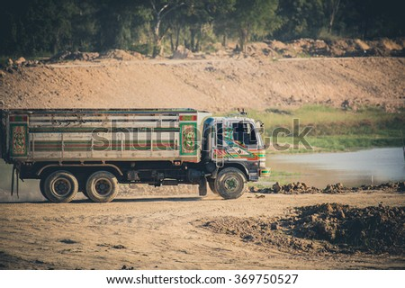 Excavator loading dumper truck tipper in sandpit in highway construction site , Yellow excavator loading soil into a dumper truck on construction site