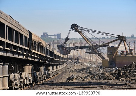 Excavator loading iron ore into goods wagon on the iron ore opencast mine - stock photo