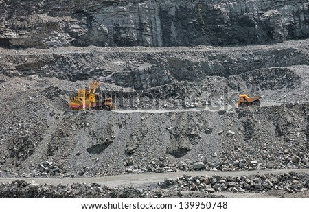 Excavator loading iron ore into the heavy dump truck on the iron ore opencast mine - stock photo
