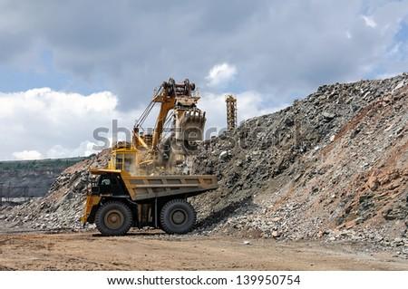 Excavator loading iron ore into the heavy dump truck on the iron ore opencast mine - stock photo