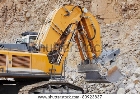 Excavator loading the crushed stone in quarry