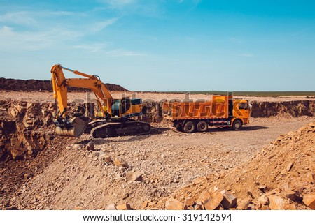 Excavator Loads Gravel into a Truck on a Crushed Stone Quarry