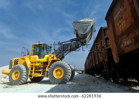 excavator loads gravel into the car of a train - stock photo